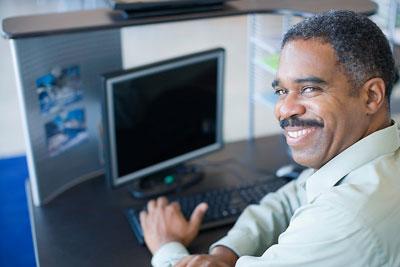A man smiling next to a laptop