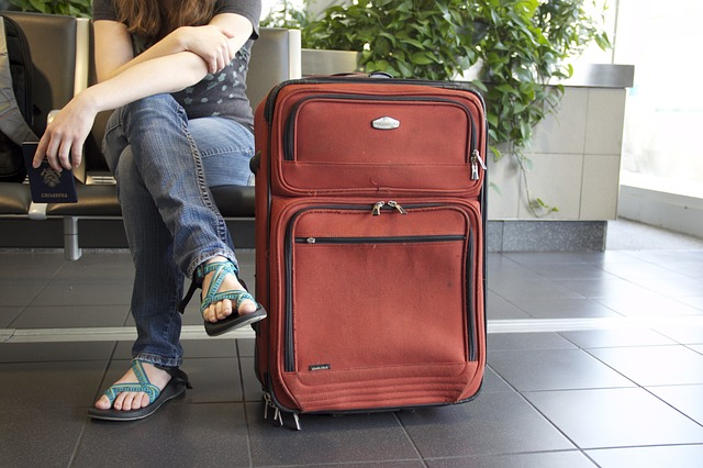 Person seated with suitcase next to them
