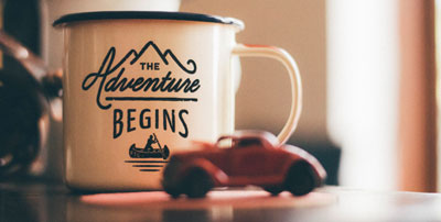 """A cup of coffee that says """"the adventure begins"""""""