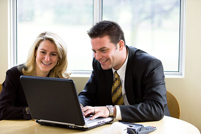 Two people talking around a laptop