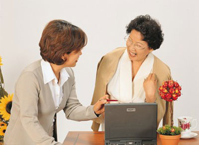 Two people talking in an office while looking at a laptop