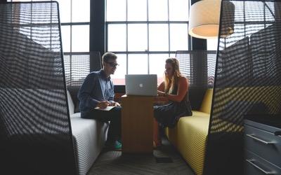 Two people talking near a laptop