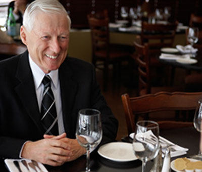 A man smiling at a dinner table business meeting