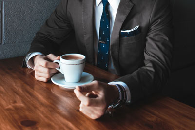 A person in a suit drinking coffee